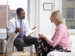 Doctor Discussing Medication with his patient as they sit next to one another