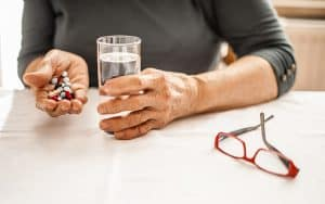 woman holding a large amount of pills in hand with a glass of water in the other hand