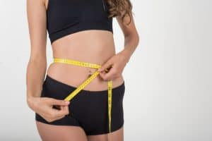 woman measuring hips and waist for properly fitting incontinence pads and products