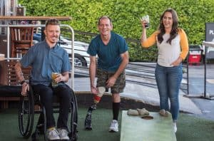 group of disabled men and a woman drinking beer and playing outdoor games