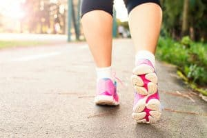 woman's calves with pink gym shoes walking on a path