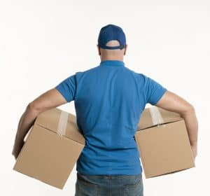 backside of a man in a blue hat and blue shirt carrying a brown box under each arm