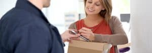 woman signing to receive a package from a delivery man