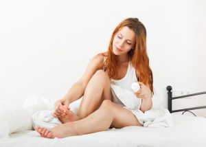 woman inspecting her toes and applying lotion as she sits on bed