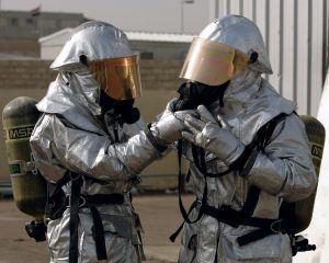 two men outfitted in protective PPE attire with face shields and breathing apparatus