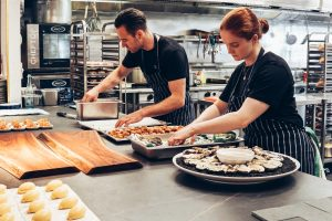 male and female chefs preparing food in the kitchen