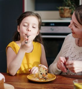 little girl in yellow dress eating dessert with her mother