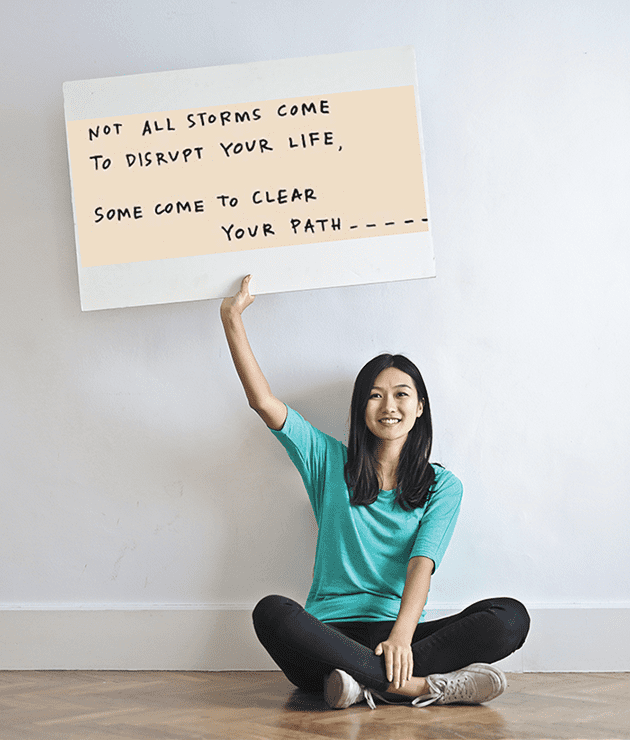 asian woman sitting on the floor holding a sign that portrays staying optimistic.