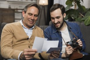 father and adult son looking at pictures as son holds a camera