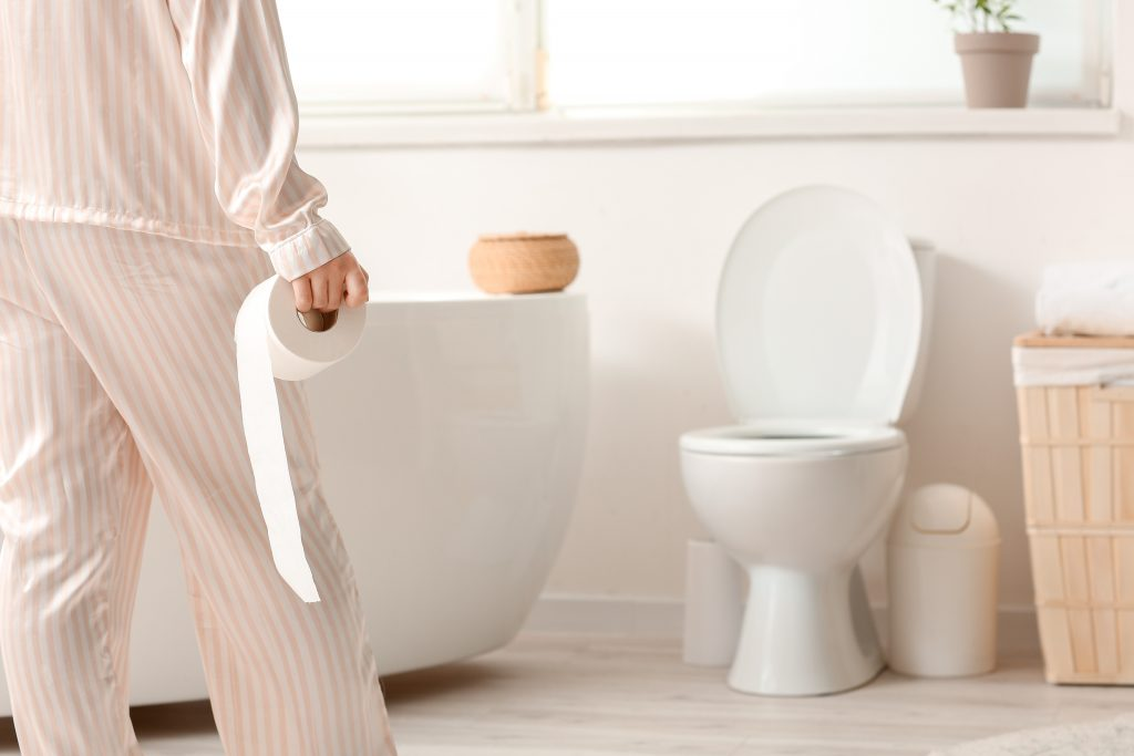 woman holding a roll of toilet paper as she walks to the toilet