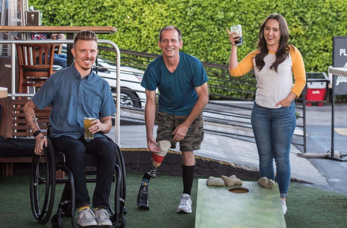 group with disabilities from spinal cord injury sharing a beer and playing games