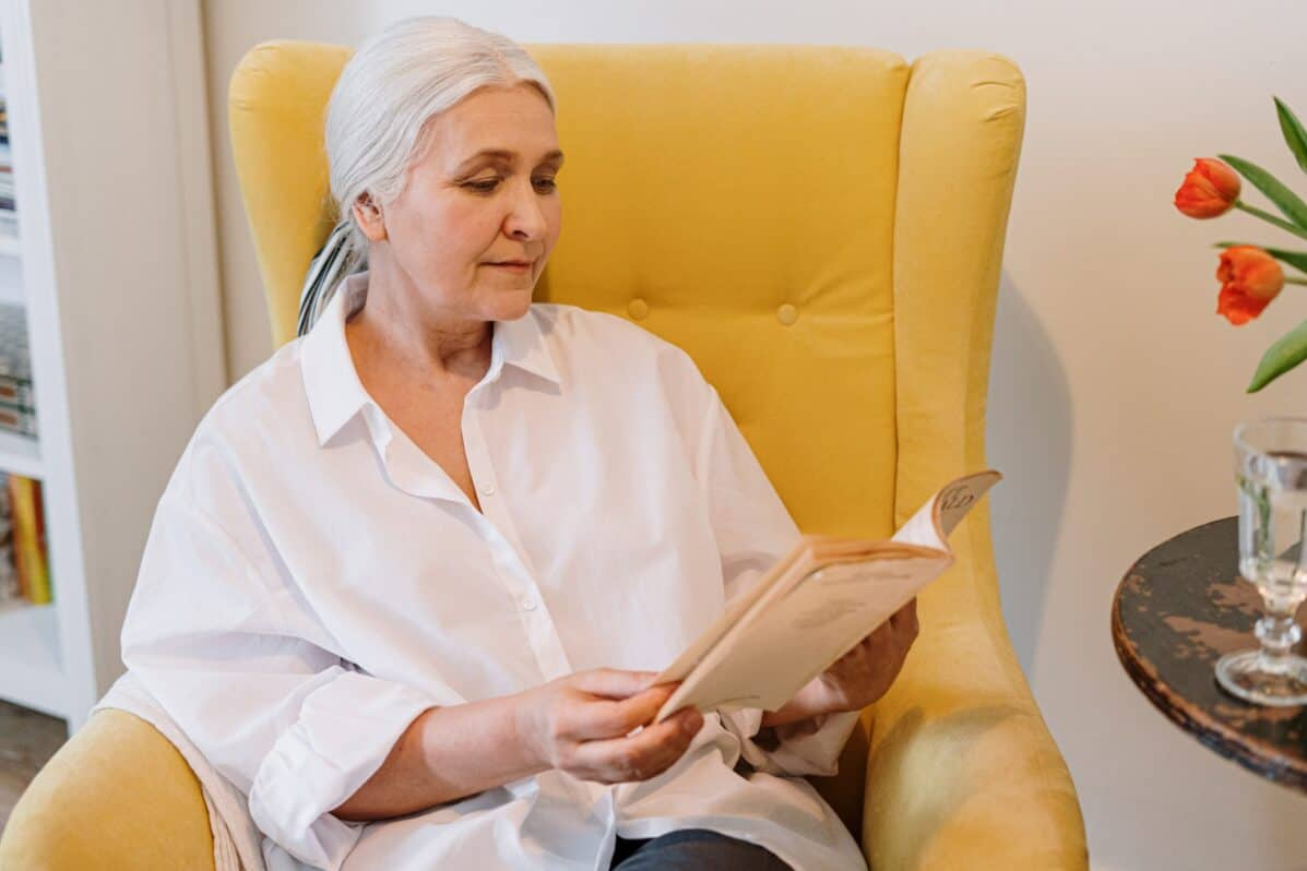 woman relaxing on a chair and reading a book