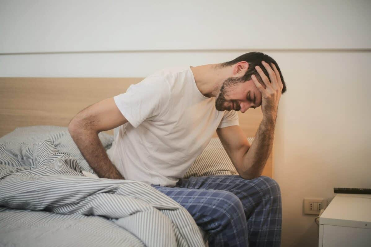 man sitting on the edge of the bed not feeling well and holding his head in his hand